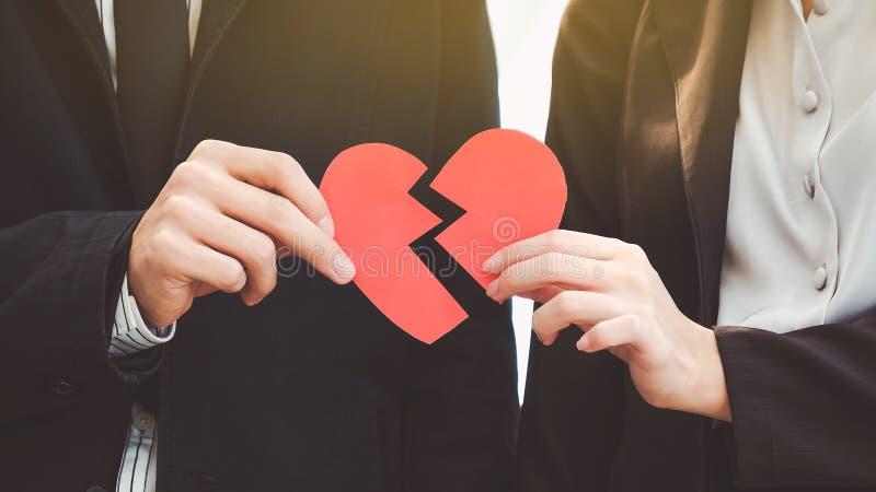 Man och kvinna som ifrån varandra drar en röd pappers- hjärta Begreppet av FN royaltyfri foto
