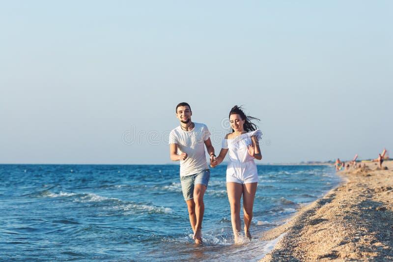 Man och kvinna som körs lyckligt längs kustlinjen av havet royaltyfria foton