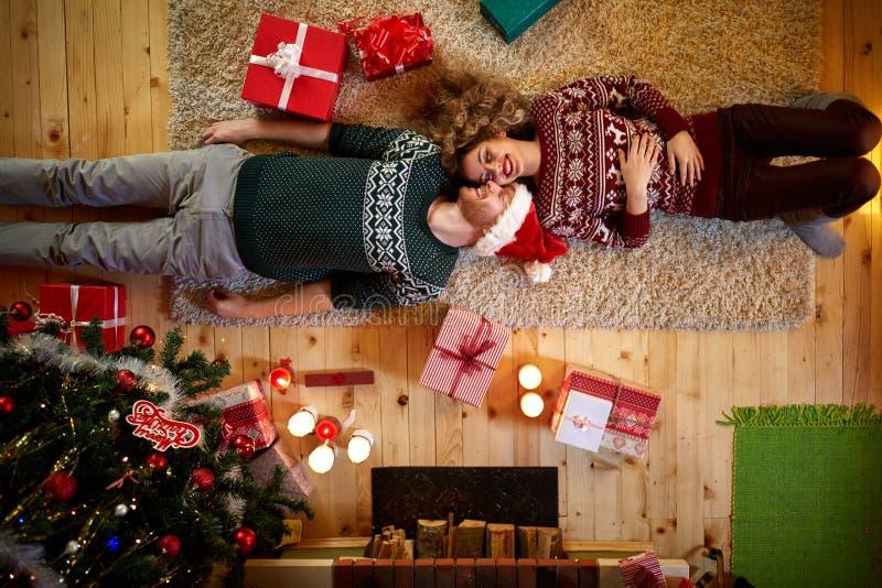 Man och kvinna som ligger på golvet för jul, bästa sikt arkivfoto