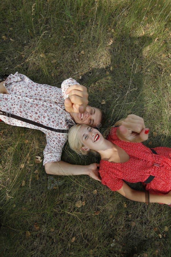 Man och kvinna som ligger på gräset arkivfoton