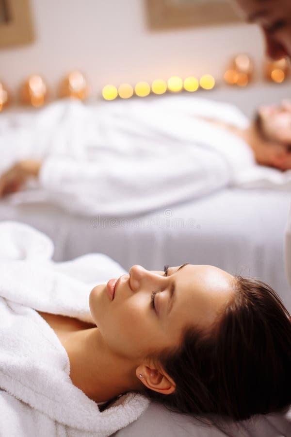 Man och kvinna som ner ligger på massagesängar på den lyxiga brunnsort- och wellnessmitten royaltyfri bild