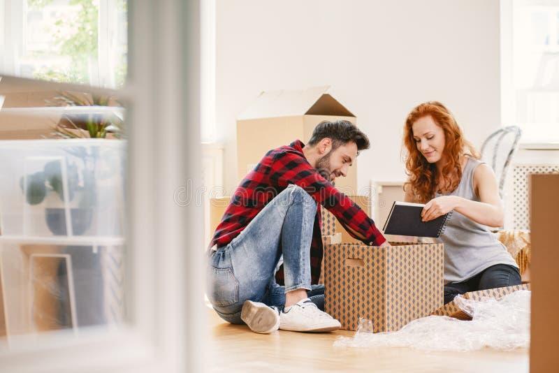 Man och kvinna som packar upp material efter förflyttning till det nya hemmet royaltyfri bild