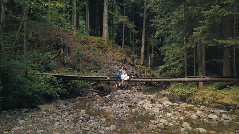 Man och kvinna som ?r f?r?lskade p? en bro ?ver floden i skog arkivfoto