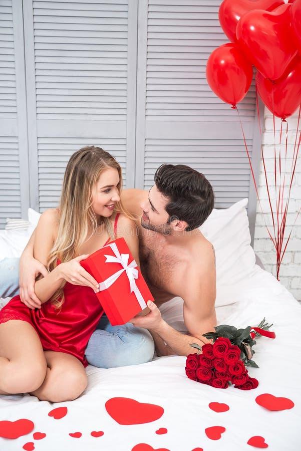 Man och kvinna som rymmer den stora röda gåvaasken arkivfoto