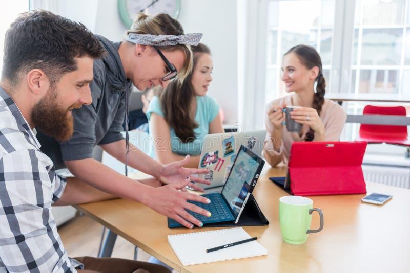Man och kvinna som samarbetar som medarbetare i kollaborativt kontor royaltyfria bilder