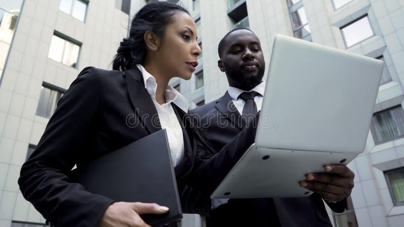 Man och kvinna som ser bärbara datorn utanför byggnad, advokater, splitterny tecken royaltyfri fotografi