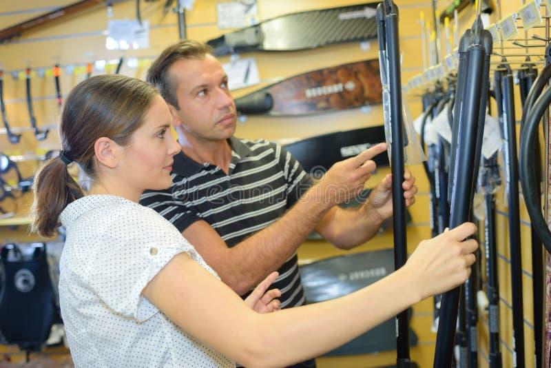 Man och kvinna som ser watersportsutrustning fotografering för bildbyråer