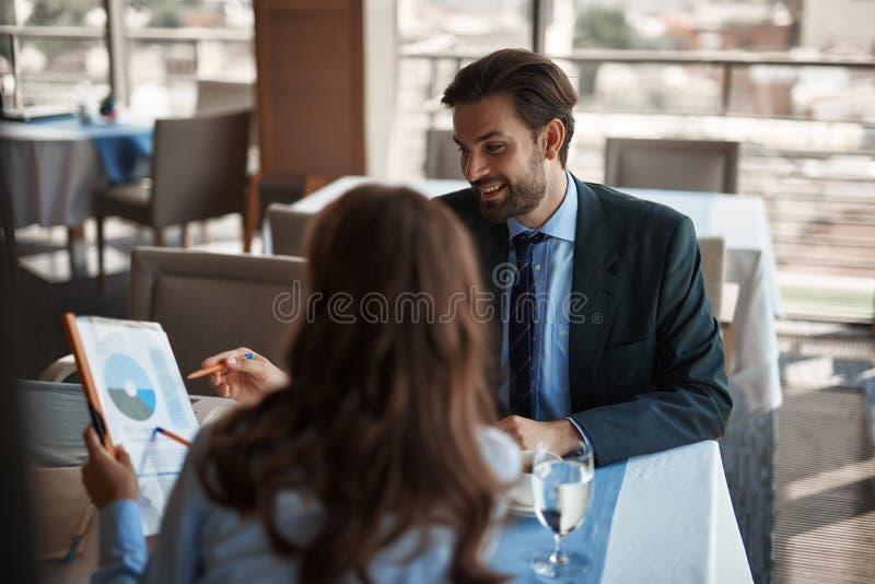 Man och kvinna som talar om arbetsprojekt i restaurang royaltyfri bild