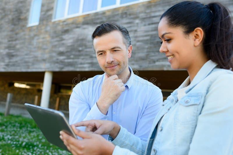 Man och kvinna som tittar på tabletten står utanför byggnaden royaltyfri foto