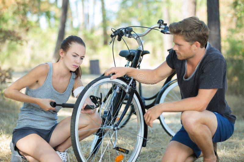 Man och kvinna som upp pumpar cykeln fotografering för bildbyråer
