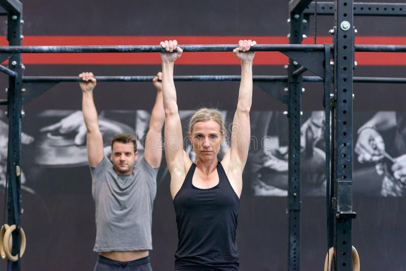 Man och kvinna som utarbetar på arga stänger i en idrottshall arkivfoton