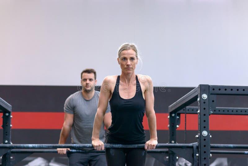 Man och kvinna som utarbetar på arga stänger i en idrottshall arkivbild