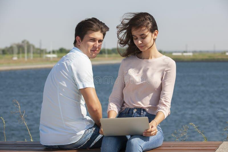 Man och kvinna som utomhus anv?nder b?rbara datorn Bild av den unga den parmannen och kvinnan i tillfällig kläder royaltyfri bild