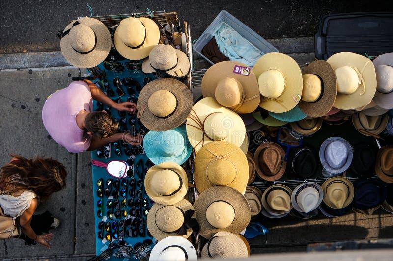 Man och kvinna som väljer exponeringsglas för dem nära tabellen med hattar och exponeringsglas på gatan Sommar Dagsljus royaltyfria bilder