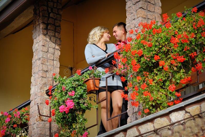 Man och kvinna tillsammans på balkong av deras hus arkivfoton