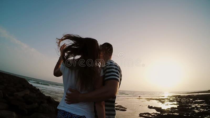Man- och kvinnaanseende på kusten av havet som kramar och håller ögonen på på solnedgång Par på aftonstranden Ultrarapider