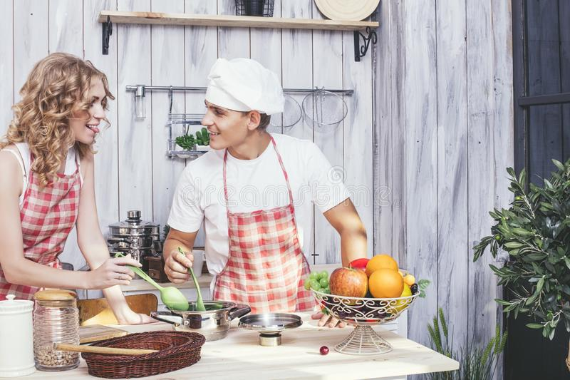 Man- och kvinnabarnet och härliga par i kökhemmet kuttrar royaltyfri fotografi