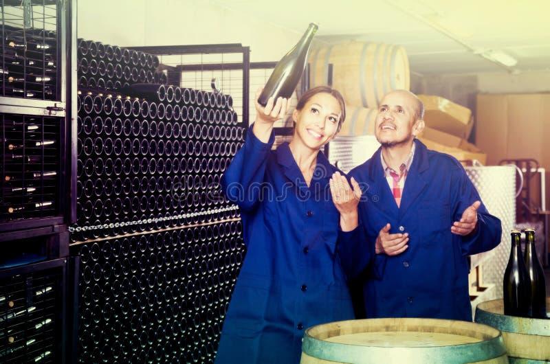 Man- och kvinnacoworkers som ser bubbligt vin i flaskstandin arkivbilder