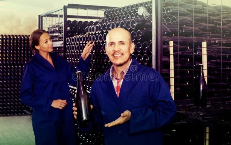 Man- och kvinnacoworkers som ser bubbligt vin i flaskstandin arkivfoto