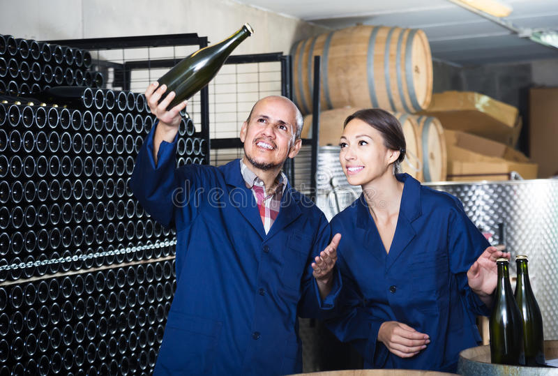 Man- och kvinnacoworkers som ser bubbligt vin i flaskstandin royaltyfria bilder
