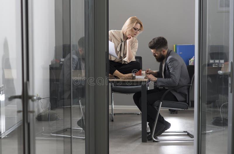Man- och kvinnaentreprenörer som skriver affärsidéer på papper Affärsaktieägare som i regeringsställning diskuterar affärsidéer royaltyfri bild