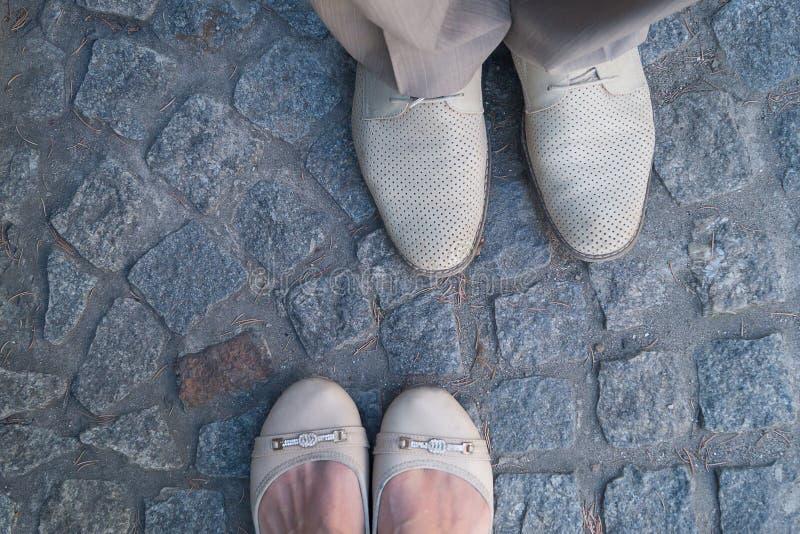 Man- och kvinnaframsida - till - framsidaställning på kullersten Fokus på skodonet arkivfoton