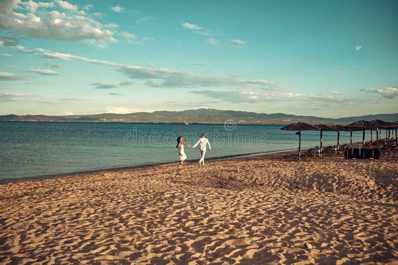 Man- och kvinnahållhänder, kopplar ihop lyckligt på semester Förälskad ställning för par på stranden, kust Bröllopsresa som preci royaltyfria bilder