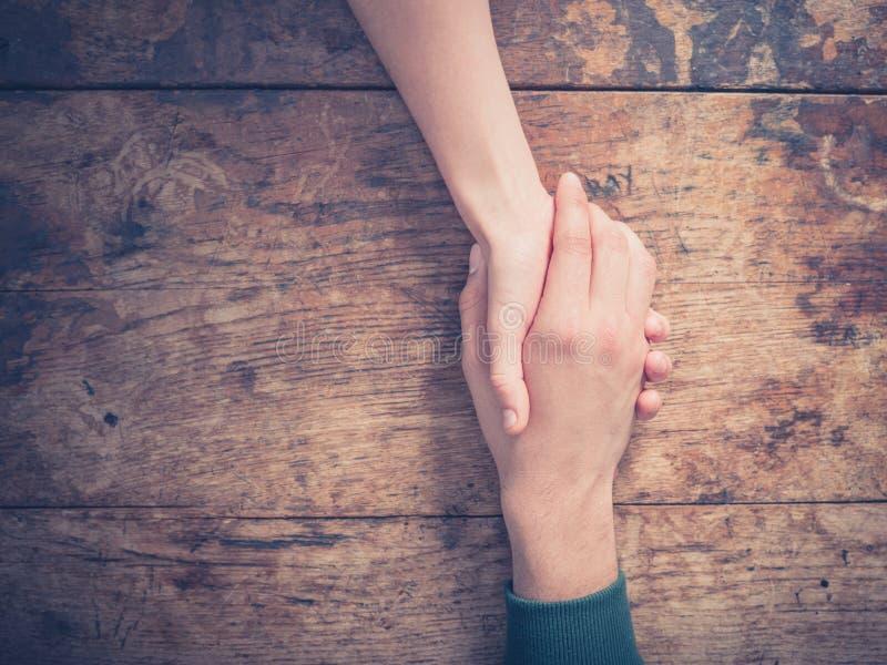 Man- och kvinnainnehavhänder på en tabell arkivfoto