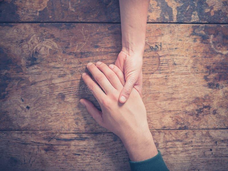 Man- och kvinnainnehavhänder på en tabell royaltyfri bild