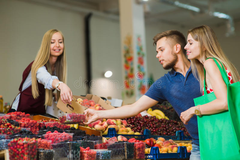 Man- och kvinnaköpbär på marknaden arkivbild