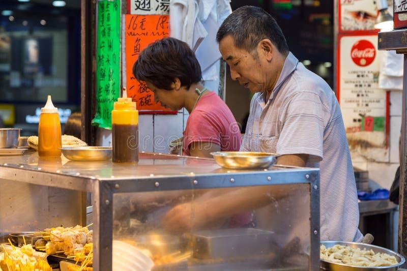 Man- och kvinnamatlagningmellanmål på en mat stannar i Hong Kong fotografering för bildbyråer