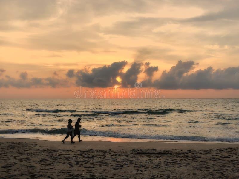 Man- och kvinnaparspring som skojar på stranden på kontur för solnedgångskymninghimmel arkivbilder