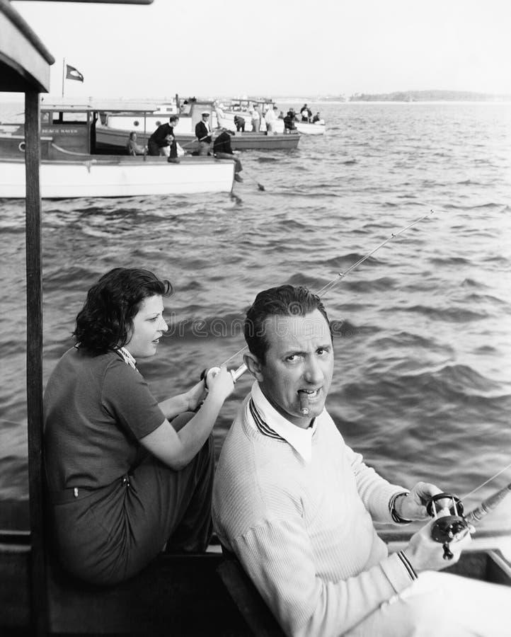 Man- och kvinnasammanträde på ett fartyg på en sjö med deras metspö (alla visade personer inte är längre uppehälle, och inget god arkivbild