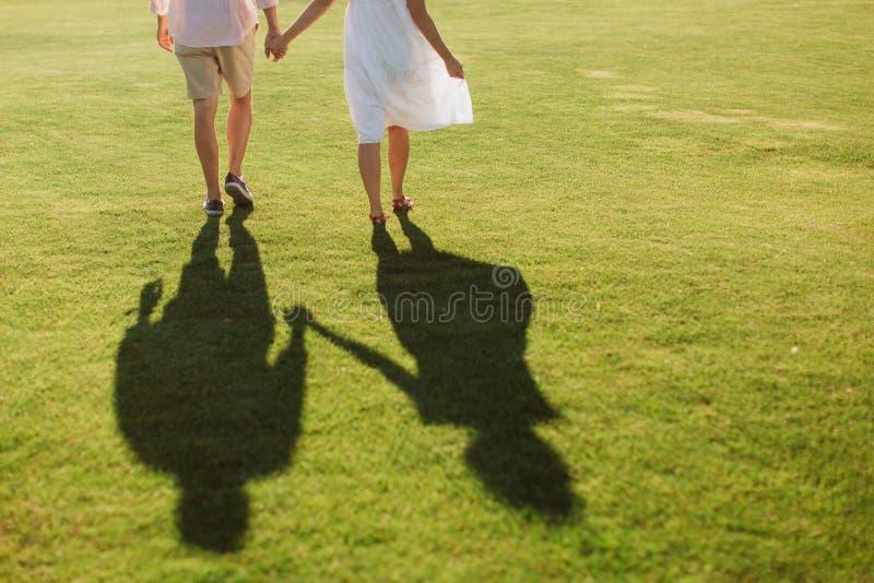 Man- och kvinnaskuggor som rymmer händer på ett grönt fält royaltyfri foto