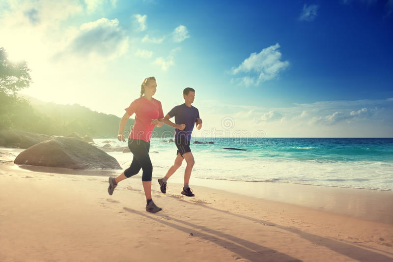 Man- och kvinnaspring på den tropiska stranden fotografering för bildbyråer