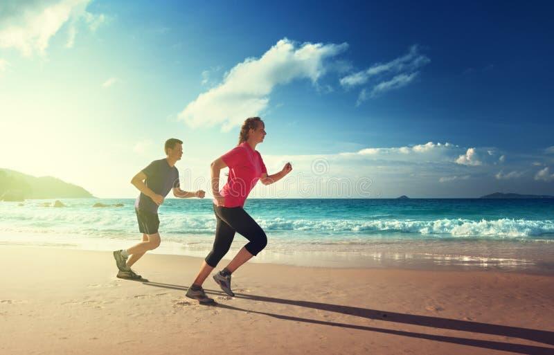 Man- och kvinnaspring på den tropiska stranden royaltyfri bild