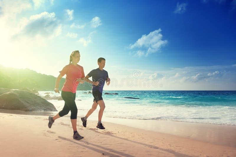 Man- och kvinnaspring på den tropiska stranden arkivbild