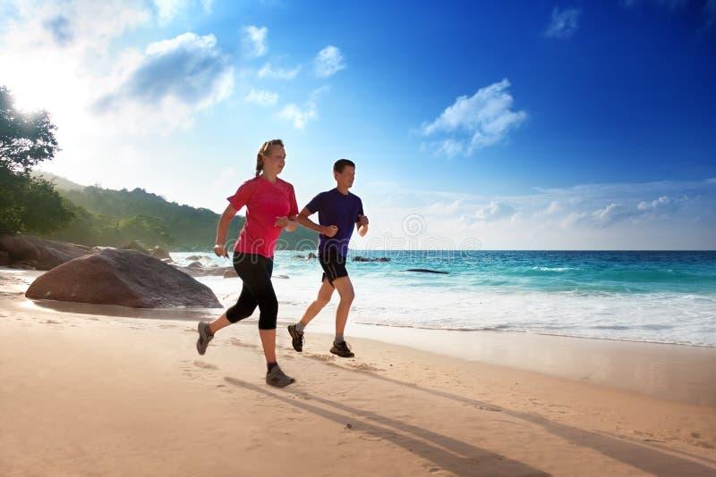 Man- och kvinnaspring på den tropiska stranden arkivfoto