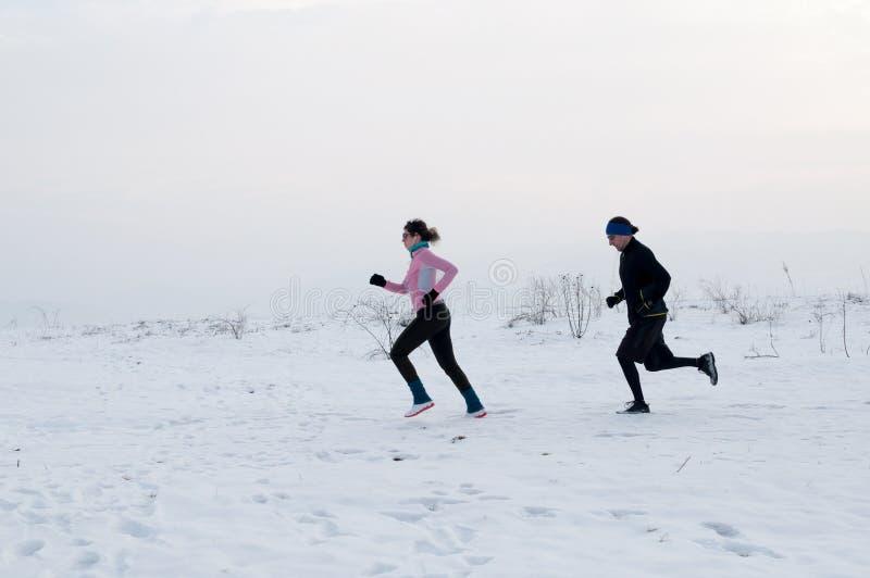 Man- och kvinnaspring på snön royaltyfri bild