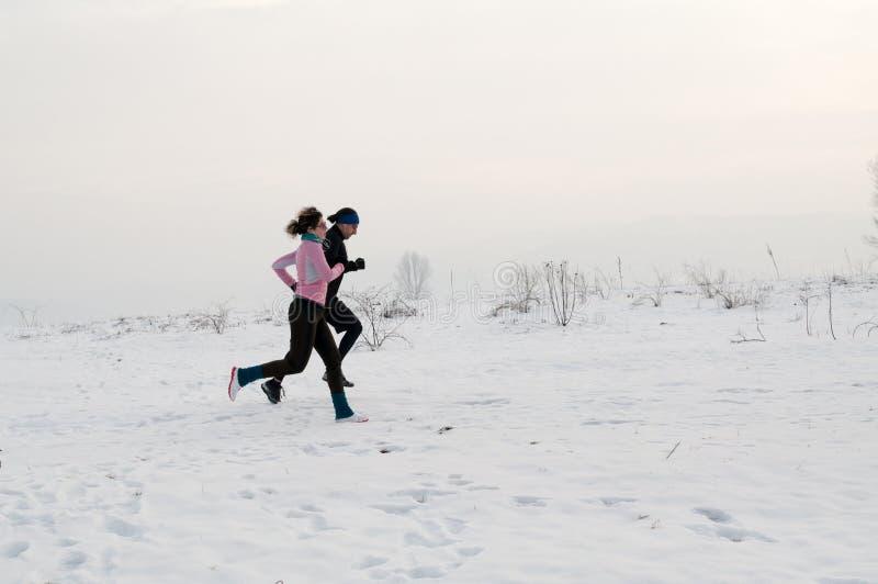 Man- och kvinnaspring på snön arkivbild