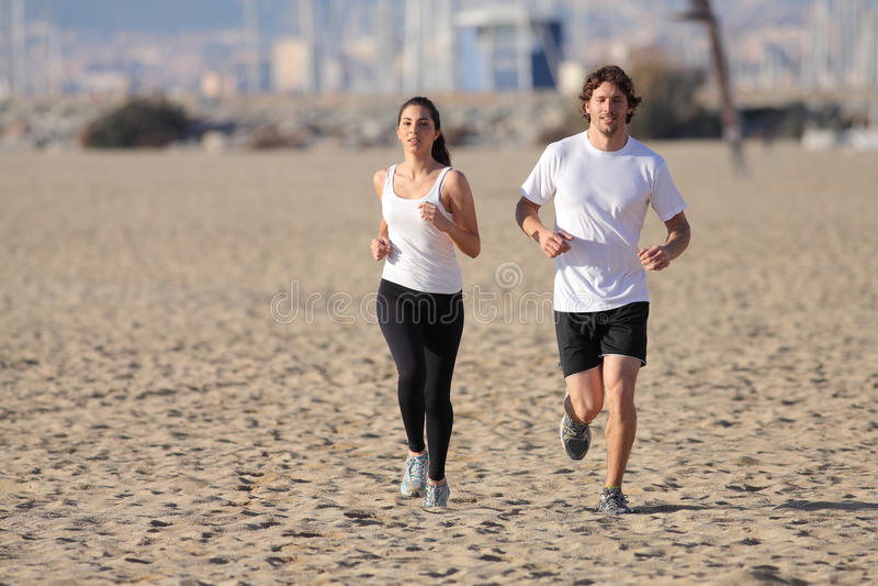 Man- och kvinnaspring på stranden arkivbild