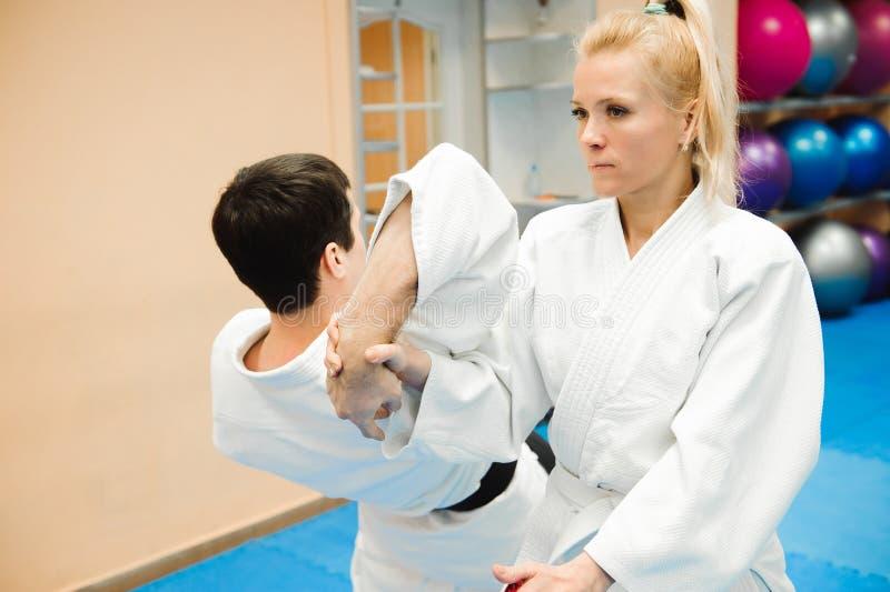 Man- och kvinnastridighet på Aikidoutbildning i kampsportskola royaltyfri fotografi