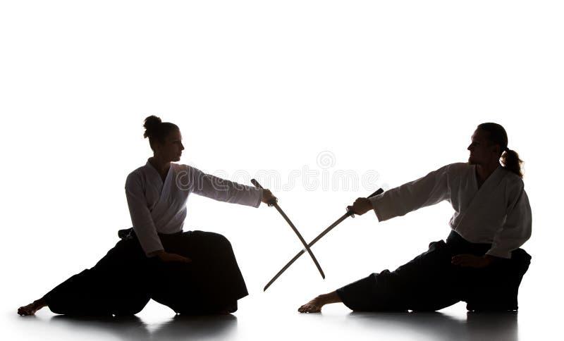 Man och kvinnastridighet- och utbildningsaikido på vit studiobakgrund royaltyfria bilder