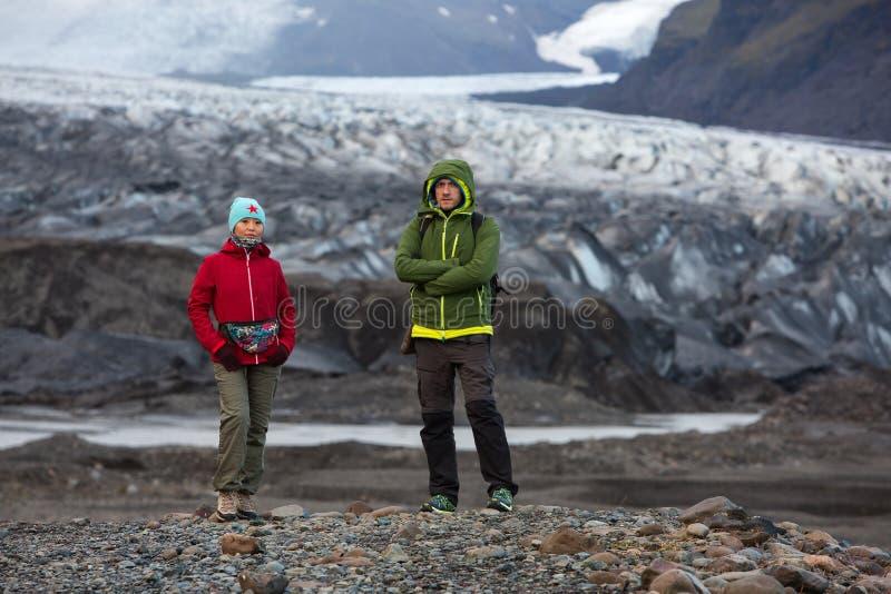 Man- och kvinnaturister står på bakgrunden av en glaciär i Island royaltyfri fotografi