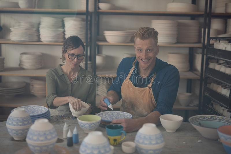 Man och kvinnlig keramiker som dekorerar bunken royaltyfri fotografi