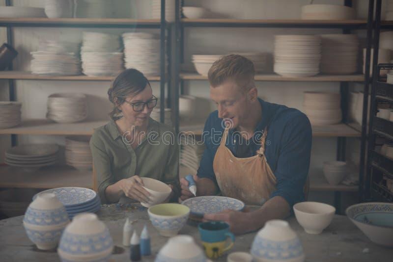 Man och kvinnlig keramiker som dekorerar bunken arkivfoto