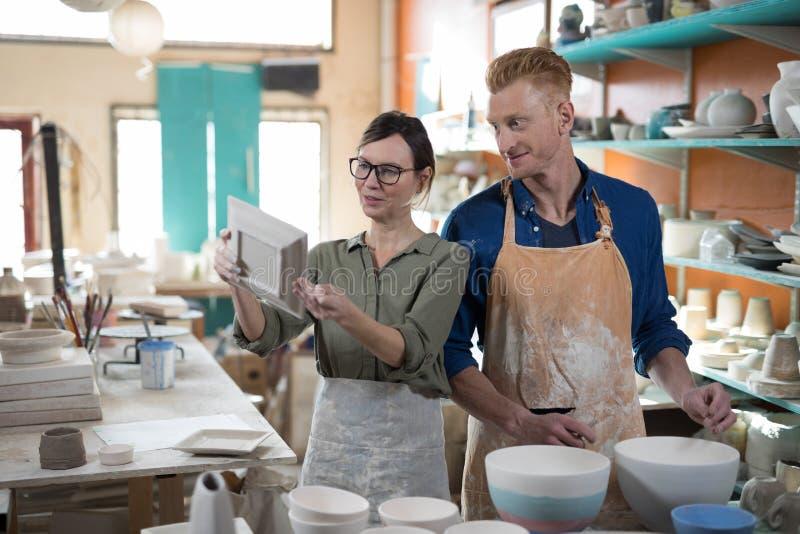 Man och kvinnlig keramiker som kontrollerar plattan royaltyfri foto