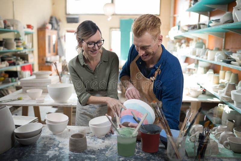 Man och kvinnlig keramiker som påverkar varandra med de arkivbild