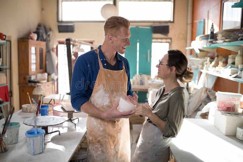 Man och kvinnlig keramiker som påverkar varandra med de royaltyfria foton