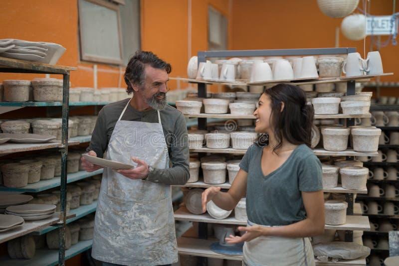 Man och kvinnlig keramiker som påverkar varandra med de royaltyfria bilder